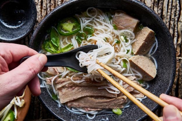 Manger du pho vietnamien avec des baguettes et une cuillère