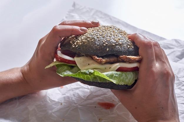Manger un hamburger noir photo recadrée d'une personne mangeant un hamburger noir à la mode délicieux hamburger avec