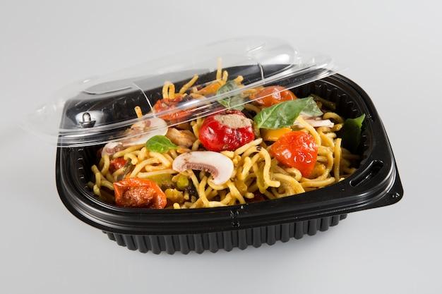 Manger lo mein hors de la boîte à emporter chinoise