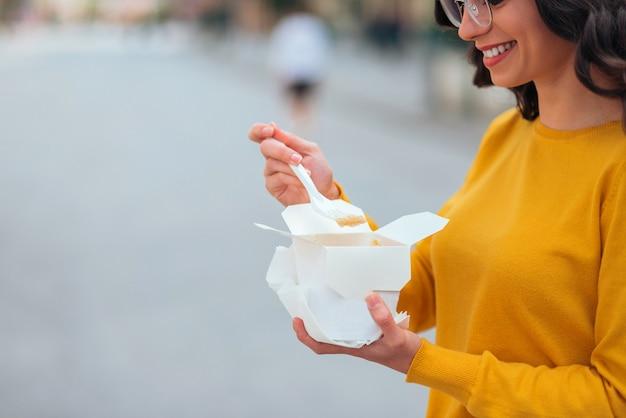 Manger de la nourriture rapide savoureuse dans une boîte de papier à emporter, gros plan, espace de copie.