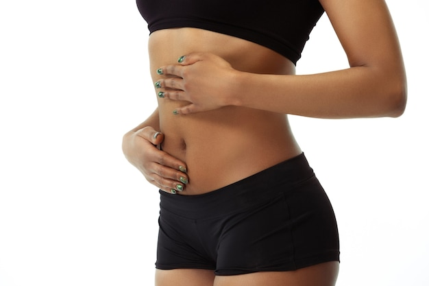 Manger, nutrition, maux d'estomac. ventre de femme bronzée mince sur mur blanc. modèle afro-américain à la forme et à la peau soignées. beauté, soins personnels, perte de poids, fitness, concept minceur.