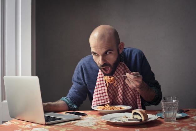 Manger des pâtes et travailler sur un ordinateur portable