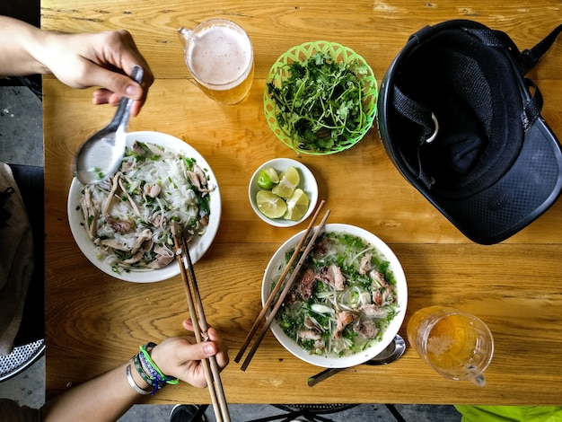 Manger la soupe pho vietnamienne avec des baguettes