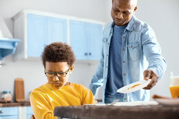 Mangez s'il vous plaît. jeune père aimant demandant à son fils de prendre son petit-déjeuner pendant que le garçon détournait le visage, montrant sa réticence