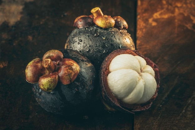 Mangoustan et coupe transversale montrant l'épaisse peau violette et la chair blanche