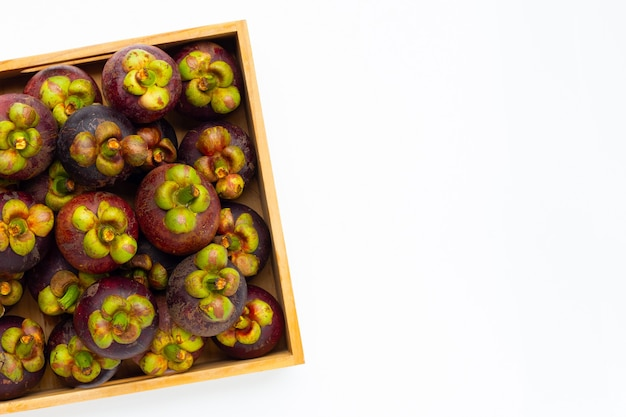 Mangoustan dans une boîte en bois sur fond blanc.
