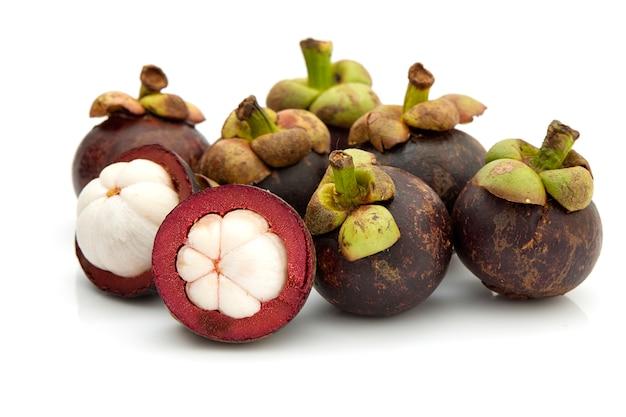 Mangoustan entier de fruits tropicaux et un autre coupé en deux sur fond blanc
