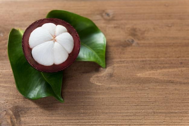 Mangoustan frais sur table en bois avec feuille verte
