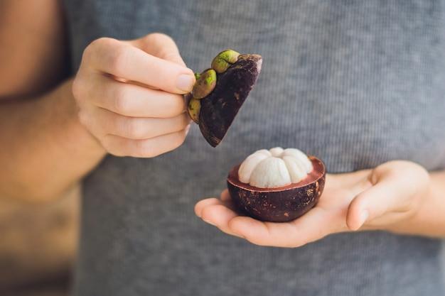 Mangoustan sur main de fermier tenir des fruits tropicaux