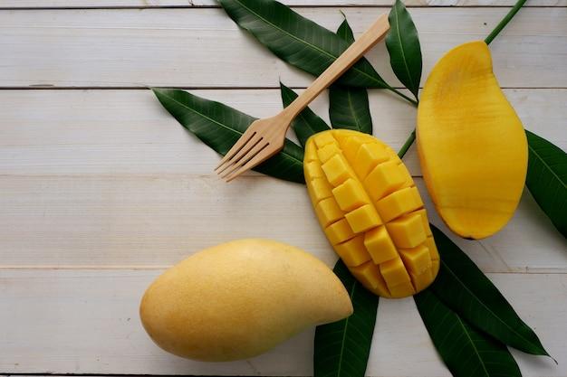 Mangue douce jaune avec une fourchette en bois sur une table en bois blanc