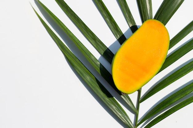 Mangue sur des feuilles de palmier tropical sur une surface blanche