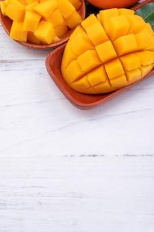Mangue fraîche, beaux fruits hachés avec des feuilles vertes sur fond de table en bois clair