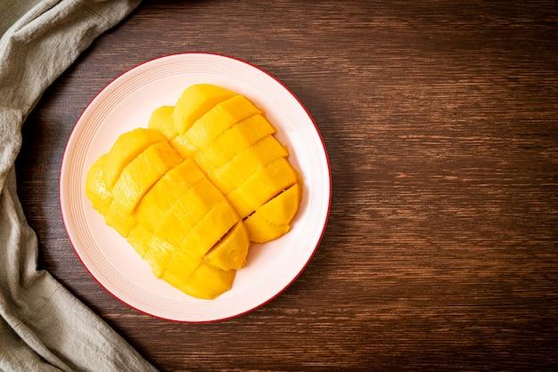 Mangue fraîche et dorée tranchée sur assiette