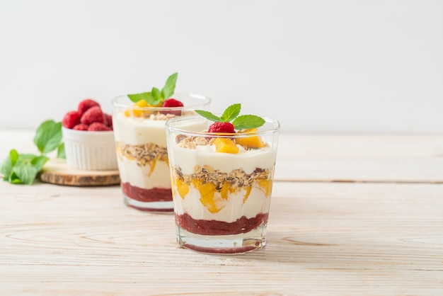Mangue fraîche faite maison et framboise fraîche avec yogourt et granola - style alimentaire sain