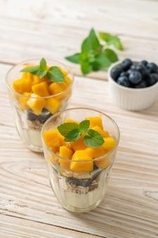Mangue fraîche faite maison et myrtille fraîche avec yogourt et granola - style alimentaire sain
