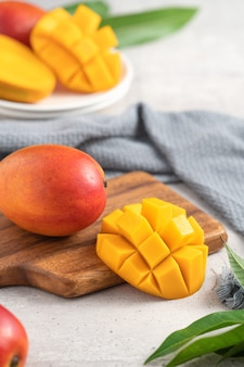 Mangue fraîche en dés sur une plaque blanche sur une planche à découper en bois avec des feuilles sur fond de table gris