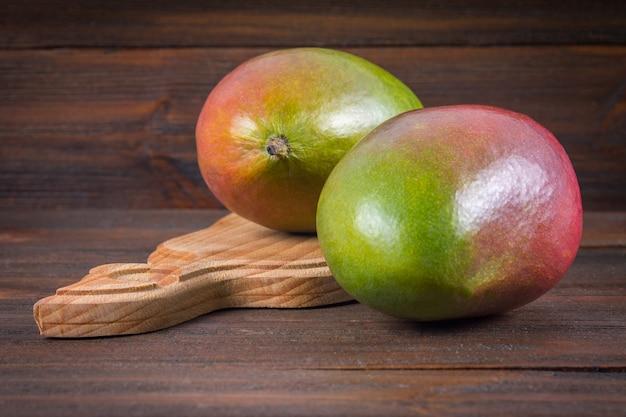 Mangue de fruits tropicaux sur un fond en bois, entier ou en tranches.