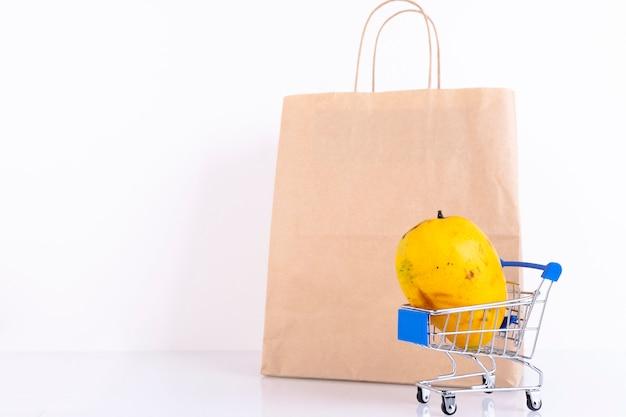 Mangue jaune dans un caddie et sac en papier artisanal sur un mur blanc. espace de copie.