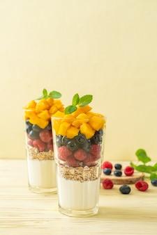 Mangue maison, framboise et myrtille avec yogourt et granola - style alimentaire sain
