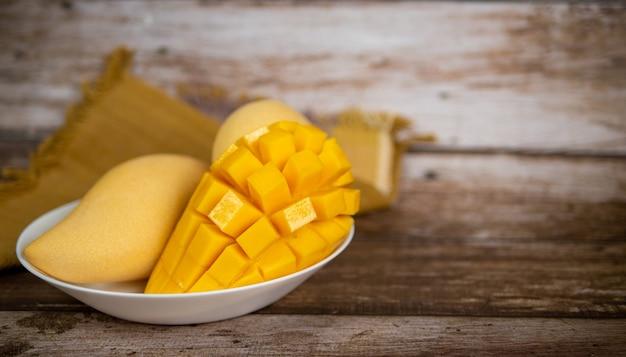 Mangue mûre coupée en cubes dans une assiette blanche avec fond en bois