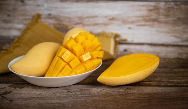 Mangue mûre coupée en dés fraîche et belle dans une assiette blanche avec fond en bois