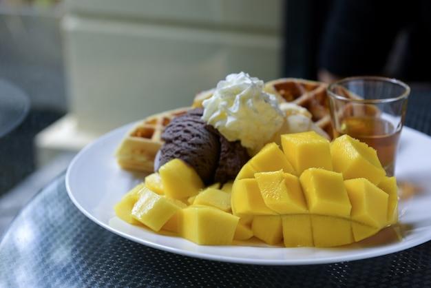 Mangue mûre, crème glacée, gaufres et miel dans un plat blanc.
