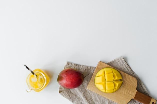 Mangue mûre, demi-mangue et un verre de jus de mangue sur une planche à découper en bois.