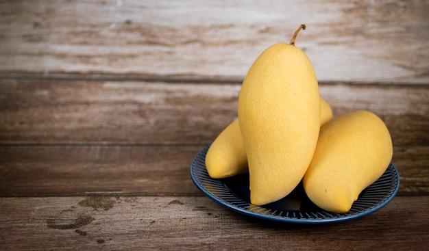 Mangue mûre fraîche et belle dans une assiette en céramique bleue avec fond en bois vertical