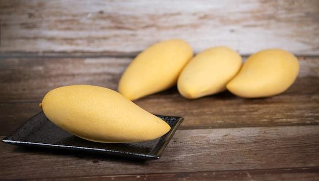 Mangue mûre fraîche et belle dans une assiette en céramique noire avec fond en bois