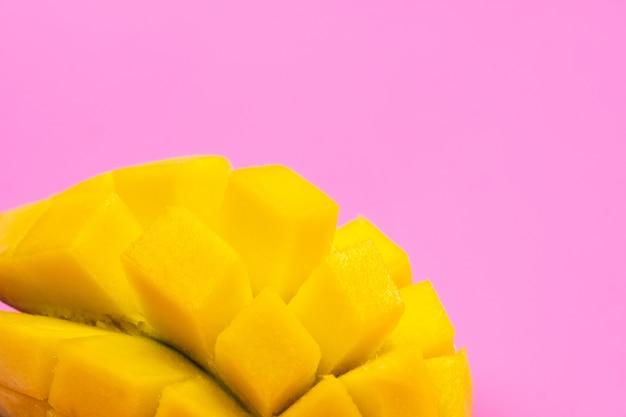 Mangue mûre fraîche sur fond rose. une demi-mangue tranchée sur fond rose.