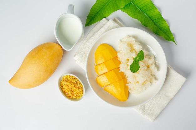 Mangue mûre fraîche et riz gluant au lait de coco sur une surface blanche