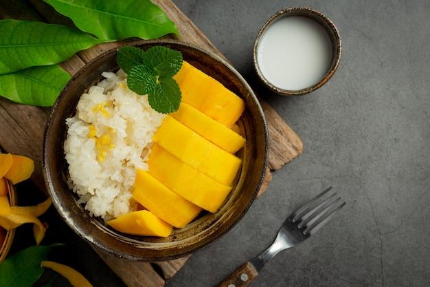 Mangue mûre fraîche et riz gluant au lait de coco sur une surface sombre