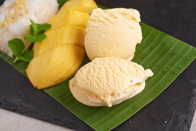 Mangue mûre et riz gluant, crème glacée au lait de coco sur la surface de la pierre, dessert sucré thaï en saison estivale. fruit exotique. dessert aux fruits. vue de dessus.