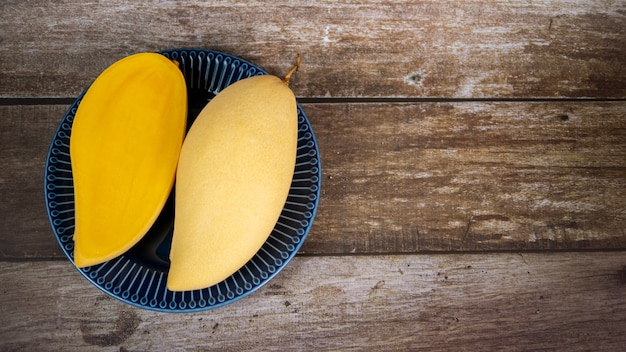 Mangue mûre tranchée fraîche et belle dans une assiette en céramique bleue avec fond en bois2