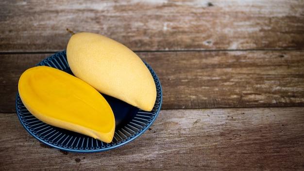 Mangue mûre en tranches fraîche et belle dans une assiette en céramique bleue avec fond en bois