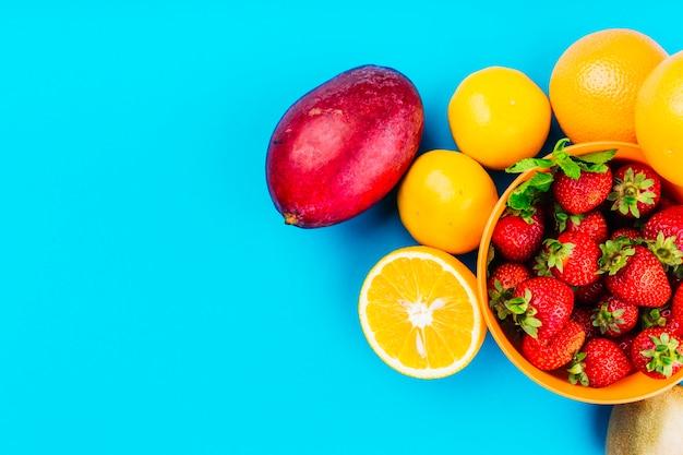 Mangue; oranges et bol de fraises sur fond bleu