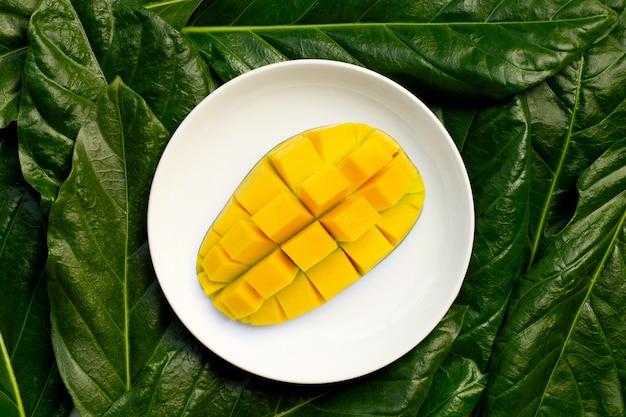 Mangue sur plaque en céramique blanche sur feuilles. vue de dessus