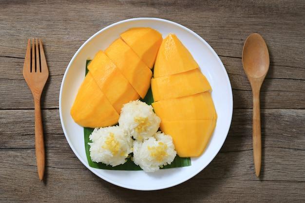 Mangue et riz gluant dans le plat blanc sur plancher en bois.