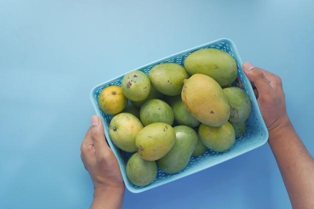 Mangue verte fraîche dans un bol sur table