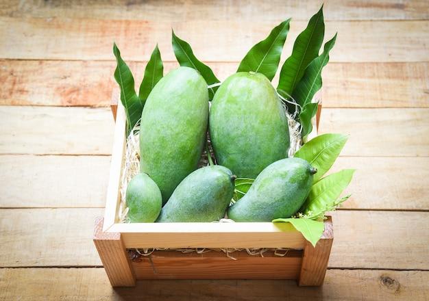 Mangue verte fraîche et feuilles vertes sur une boîte en bois