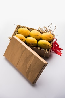 Mangues alphonso dans une boîte-cadeau sur herbe et attachées avec un ruban rouge, mise au point sélective