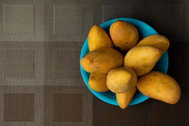 Mangues dans une assiette bleue sur une nappe marron