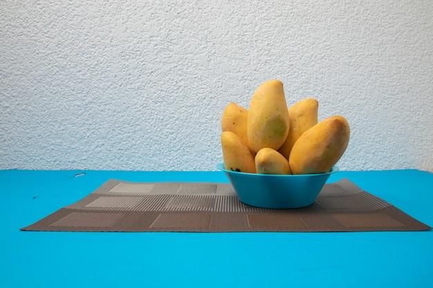 Manilles mûres de manille sur une assiette et fond de couleur bleu