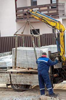 Manipulateur avec dalles dans la construction de la chaussée.