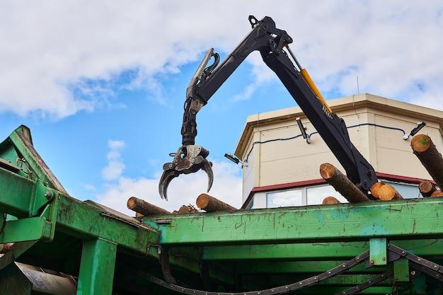 Le manipulateur hydraulique contrôlé contrôle la position des grumes sur le convoyeur d'alimentation dans une scierie moderne