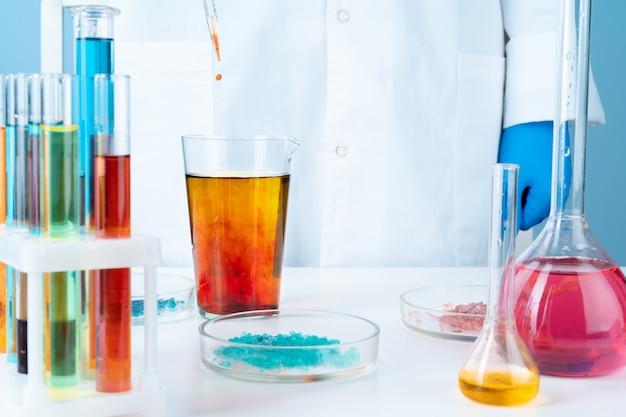 Manipulations avec des contenants de verre de laboratoire sur la table