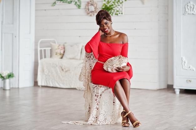 Mannequin afro-américaine en robe de beauté rouge, femme sexy posant la robe de soirée assis à la chaise dans une salle vintage blanche.
