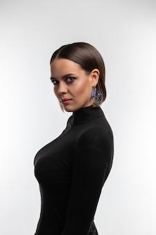 Mannequin attrayant avec maquillage fumé, cheveux noirs colorés et grands yeux posant à demi-tour et regardant