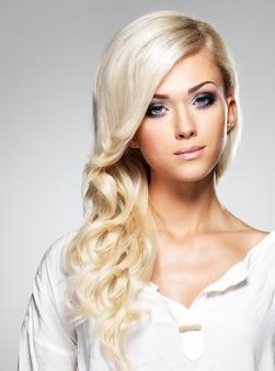 Mannequin aux longs cheveux blancs et maquillage lumineux. portrait de femme glamour