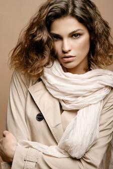 Mannequin de beauté avec une peau propre et des cheveux bouclés en cape de siège extensible avec une écharpe